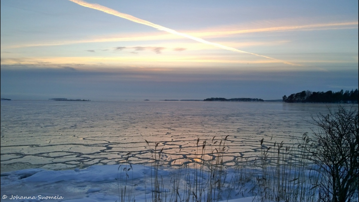 Meri jaatyy lentovanat auringonlasku